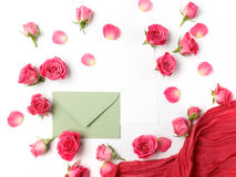 Envelop with white card and rose background. Flat lay, top view. Stock Photo