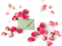 Envelop with white card and rose background. Flat lay, top view. Royalty Free Stock Image