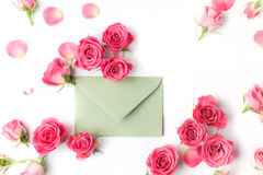 Envelop with white card and rose background. Flat lay, top view. Stock Images