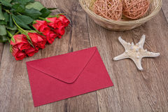 Envelop, zeester en rozen op een houten achtergrond Stock Foto