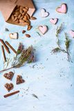 Envelope with almonds, delicious heart shaped cookies, cinnamon sticks and green branches with flowers Royalty Free Stock Photo