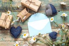 Envelope azul com camomilas e caixas de presente Espaço para o texto imagens de stock