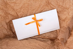 Envelope on the background of crumpled paper. Envelope with a ribbon on a background of crumpled paper Stock Images