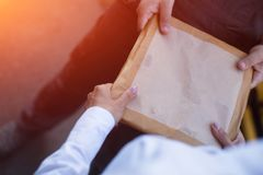 Delivery man handing envelope. Envelope being held by two pairs of hands. Female hands passing big tan envelope to men for delivery purposes Stock Images