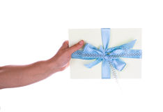 Envelope with a blue ribbon in her hand. Isolated on white Royalty Free Stock Photos