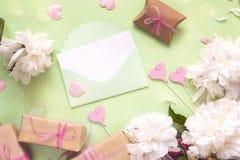 Envelope bonito verde com peônias, as caixas de presente e o deco brancos Fotos de Stock Royalty Free