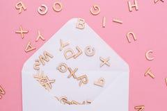 Envelope branco aberto com muitas letras do ABC no fundo cor-de-rosa imagem de stock royalty free