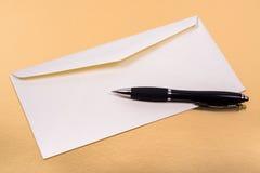 Envelope branco não lacrado com uma pena de esferográfica no lado Fotos de Stock