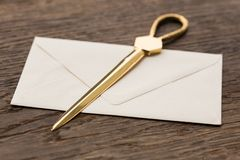 Envelope and brass letter opener on a desk Royalty Free Stock Photos