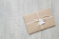 Envelope from brown craft paper decorated with ribbon and label on gray wooden background. Stock Photo