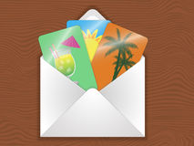 Envelope. With cards with the image of cocktails, palm trees, and sun on the wooden table royalty free illustration