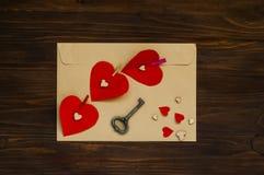 Envelope claro com corações em pregadores de roupa e uma chave em um fundo de madeira, o conceito do dia do ` s do Valentim, vist Foto de Stock Royalty Free
