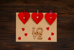Envelope claro com corações em pregadores de roupa em um fundo de madeira, o conceito do dia do ` s do Valentim, viewn superior Imagens de Stock Royalty Free