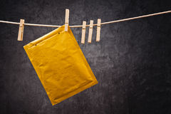 Envelope on clothes rope. Postal mail Envelope hanging on rope attached with clothes pins. Communication concept Stock Photo