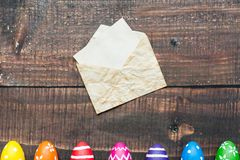 Envelope and colorful easter eggs. Mockup of a piece of paper in an envelope on dark boards with colorful easter eggs pattern Stock Images