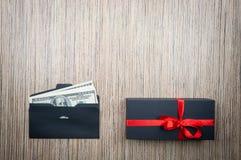 Envelope com dólares dinheiro e presente na tabela de madeira Escolha difícil da doação Copie o espaço imagens de stock royalty free