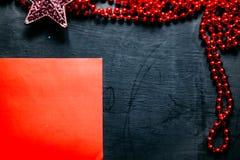 Envelope com festão vermelha e uma estrela no fundo preto imagens de stock