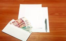 Envelope com um dinheiro e um papel vazio imagens de stock