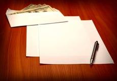 Envelope com um dinheiro e um papel vazio imagens de stock royalty free