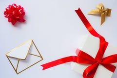 Envelope, curva dourada e caixa de presente branca com curva do cetim e r vermelhos Fotografia de Stock