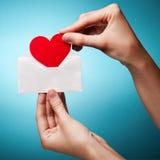 Envelope da preensão da mão da mulher com um sinal do coração Foto de Stock