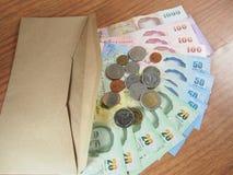 Envelope de Brown com todo o dinheiro doado Fotografia de Stock Royalty Free