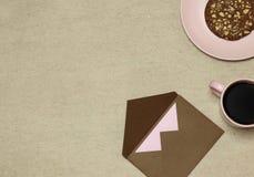 Envelope do ofício de Brown com placa, xícara de café, bolo no fundo bege imagens de stock