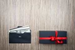 Envelope with dollars money and gift on wooden table. Difficult choice of donation. copy space royalty free stock images