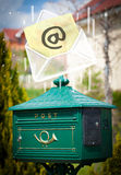 Envelope with email sign dropping into mailbox Stock Images