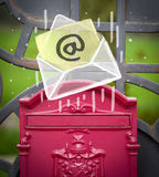 Envelope with email sign dropping into mailbox Royalty Free Stock Images