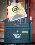 Envelope with email sign dropping into mailbox Stock Photo