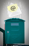 Envelope with email sign dropping into mailbox Royalty Free Stock Image