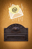 Envelope with email sign dropping into mailbox Royalty Free Stock Photos