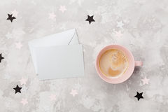Envelope with empty card and cup of coffee on womans working desk top view. Flat lay. Party invitation or greeting message. Envelope with empty card and cup of stock image