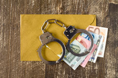Envelope with Euro bills and handcuffs Stock Images