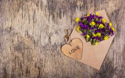 Envelope with flowers. Wildflowers in an envelope. Heart made of wood. Romantic concept. Envelope with flowers. Wildflowers in an envelope. Heart made of wood Royalty Free Stock Photography