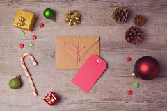 Envelope and gift tag with Christmas decorations on wooden background. View from above Royalty Free Stock Photography