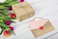 Envelope and gift for your loved one. Tulips, a gift and an envelope for your loved one, just enter your text on the pink paper royalty free stock photos