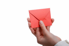 Envelope in hand. Hand holding a red envelope on a white background Stock Photography