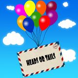 Envelope with HEADS OR TAILS message attached to multicoloured balloons on blue sky and clouds background. Stock Photos
