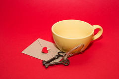 Envelope with heart, two keys and yellow cup on a red background. Mailing Envelope with heart, two vintage key and yellow cup on a red background royalty free stock images