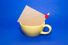 Envelope with heart in the yellow cup on a blue background. Mailing Envelope in the yellow cup on a blue background stock images
