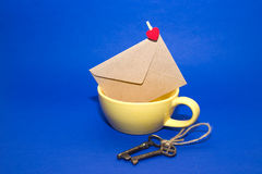 Envelope with heart in the yellow cup and two keys on a blue ba. Mailing Envelope with heart is in the yellow cup and two keys on a blue background stock photos
