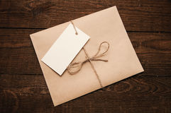 Envelope from kraft pape. Note from a paper on a cord of an envelope from kraft paper on a wooden table Stock Images
