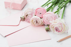 Envelope or letter, paper card, gift and pink ranunculus flowers on white table for greeting on Mother or Woman Day. Stock Images