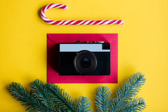 Envelope and lolipop with retro camera. Red christmas envelope and lolipop with retro camera on yellow background Stock Images