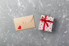 Envelope Mail with Red Heart and gift box over grey cement Background. Valentine Day Card, Love or Wedding Greeting Concept.  stock photos