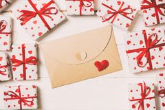 Envelope Mail with Red Heart and gift box over Wooden vintage toned Background. Valentine Day Card, Love or Wedding Greeting. Concept design stock image