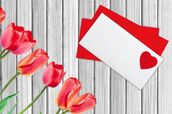 Envelope Mail and Red Tulips, Over White Wooden Background Royalty Free Stock Image