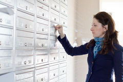 Envelope in mailbox. Woman inserting envelope with advertising material in mailbox in residential building stock photos